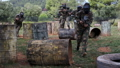 team of adult people playing on paintball battlefield outdoor  77255868