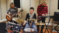 Music garage band with expressive girl drummer rehearsing in sound studio 77255888
