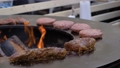 Slow motion: grilling meat steaks and cutlets on brazier with hot flame 77266086