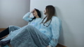 Tired female doctors sit on the floor in the hospital near the wall during the covid-19 pandemic 77275234