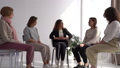 Young woman introduces herself and talks about herself at a therapeutic women's group meeting led by a psychotherapist 77275309