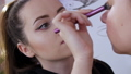 The stylist make-up master makes an eye on the evening stylish bright makeup on a young girl model in a beauty studio, a special brush paints with eye shadows using a special brush 77316623