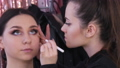 The stylist make-up master applies a foundation or concealer on the face of a young girl model using a special brush 77316625