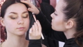 The stylist make-up master makes an eye on the evening stylish bright makeup on a young girl model in a beauty studio, a special brush paints with eye shadows using a special brush 77316627