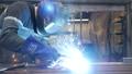 The welder cooks the frame. The welder cooks the metal. The welder cooks metal structures. Welding works. Sparks, molten metal 77316862