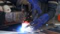 The welder cooks the frame. The welder cooks the metal. The welder cooks metal structures. Welding works. Sparks, molten metal 77316865
