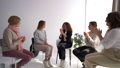 A woman tells her story in a psychotherapist's office during group therapy. Other therapy participants applaud. Female circle concept, psychologist profession 77317075
