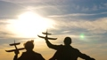 Silhouette of children playing on plane. Children in front of the sky and the sun with an airplane in hand. Dreams of flying. Happy childhood concept. Two girls play with a toy airplane at sunset. 77333929