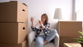 Girl throws up papers. Mature single young woman is sitting in her new home among cardboard boxes and counting bills. Real estate prices and relocation concept 77349679