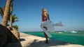 Pretty young woman in white pareo standing on pier near sea 77449446