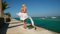 Pretty young woman in white pareo standing on pier near sea 77449455