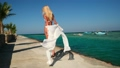 Pretty young woman in white pareo standing on pier near sea 77449458