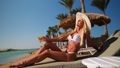 Sexy woman wearing bikini sitting on lounger under straw canopy umbrella at the beach holding glass with cocktail or drink 77449459