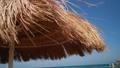 A straw umbrella on a beautiful beach 77449472