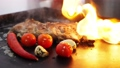 The ribs with vegetables roasts on the grill, slow motion. 77449833