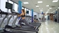 Young sporty Woman On Running Machine In Gym 77449979