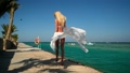 Pretty young woman in white pareo standing on pier near sea 77449996