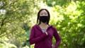 マスクを着用してジョギングする女性 77472933
