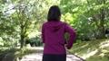 公園をジョギングする女性 77472936