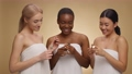 Three diverse women wrapped in towels discussing new lipsticks, laughing together over beige studio background 78052888