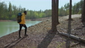 A young black man in a yellow cursor climbs up with a backpack uphill in the woods looking at the 78093203