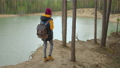 A young black woman in a yellow cursor climbs up with a backpack uphill in the woods looking at the 78093206