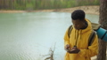 A black man is walking on top of a mountain and typing a message and photo on his smartphone. He has 78093215