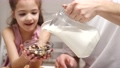 Caring father and little daughter add milk to cornflakes 78389881