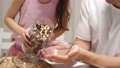 Caring father and little daughter add milk to cornflakes 78389882