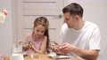 Caring father and little daughter add milk to cornflakes 78389883
