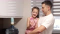 Man holding daughter in hands standing in kitchen 78390062