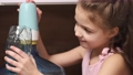Little girl getting water from a cooler 78390063
