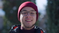 Close-up of smiling young handsome Caucasian man exhaling warm breathe on frosty winter day outdoors looking at camera. Portrait of cheerful millennial in eyeglasses posing in forest travelling 78448429