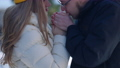 Close-up boyfriend warming girlfriend hands with breathe standing in sunny winter forest smiling. Loving Caucasian couple kissing travelling outdoors on cold day. Love and tourism 78448432