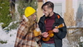Young man playing ukulele singing serenade for smiling woman holding coffee tea cup outdoors on sunny winter day. Smiling loving Caucasian boyfriend serenading girlfriend. Music and love 78448437