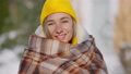 Headshot portrait of happy young woman in yellow hat wrapping in blanket standing outdoors looking at camera. Close-up face of cheerful beautiful slim millennial posing on winter day in slow motion 78448439