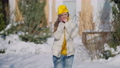 Young freezed Caucasian woman standing outdoors on winter day talking on the phone. Portrait of slim beautiful millennial waiting on sunny day on frosty backyard. Lifestyle and weather 78448442
