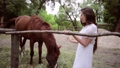 Young woman on a ranch is stroking a horse. 78487382