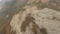 Mountain bare top with brown rocky cliffs and dense thickets 78494900