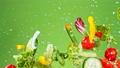 Super Slow Motion Shot of Flying Fresh Vegetables and Water Splash on Green Gradient Background at 1000fps. 78531954