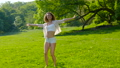 A young beautiful woman dancing on the grass in the park 78543777