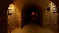 The camera moves along the corridor of the stone dungeon 78564828