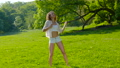 A young beautiful woman dancing on the grass in the park 78564830