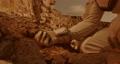 Unrecognizable cosmonaut examining soil on Mars 78576609