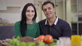Portrait of happy smiling Caucasian woman and Middle Eastern man looking at camera sitting at dinner table indoors. Loving interracial couple posing at home in the evening. Love and unity concept 78672885