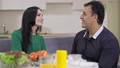 Side view portrait of happy loving interracial couple talking and smiling discussing day in the evening at home indoors. Adult Caucasian woman and Middle Eastern man chatting resting at dinner 78672886