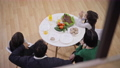 High angle view of relaxed happy family sitting at dinner table talking. Middle Eastern man Caucasian woman and twin boys discussing weekend at home indoors. Family joy 78672888