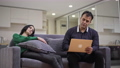 Concentrated absorbed Middle Eastern man typing on laptop keyboard as bored Caucasian woman sitting on couch. Portrait of handsome adult businessman ignoring beautiful wife at home 78672897