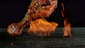 Super slow motion of chicken legs with falling herbs and spice with fire on black background. 78702646