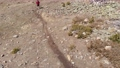Aerial view of a young man in a cap, sunglasses, shorts with a backpack on his shoulders, walks in the mountains along a ladder. Threatens the drone with a stick. Drone ban humor 79027770